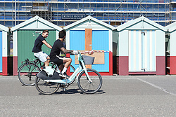 © Licensed to London News Pictures. 25/04/2020. Brighton, UK. Two people ride bikes on Brighton seafront at Brighton and Hove, during a pandemic outbreak of the Coronavirus COVID-19 disease.  Photo credit: Liz Pearce/LNP