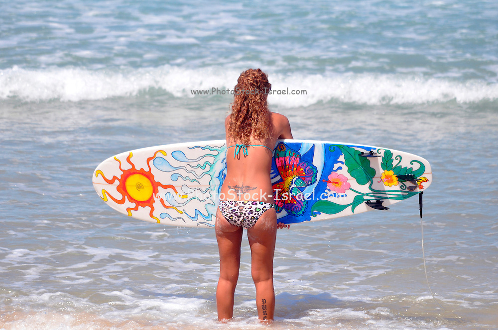 Female Surfer enters the Mediterranean sea holding her surfboard