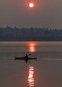 A kayaker takes in a smokey morning sunrise on Lake Washington off Magnuson Park. (Steve Ringman / The Seattle Times)