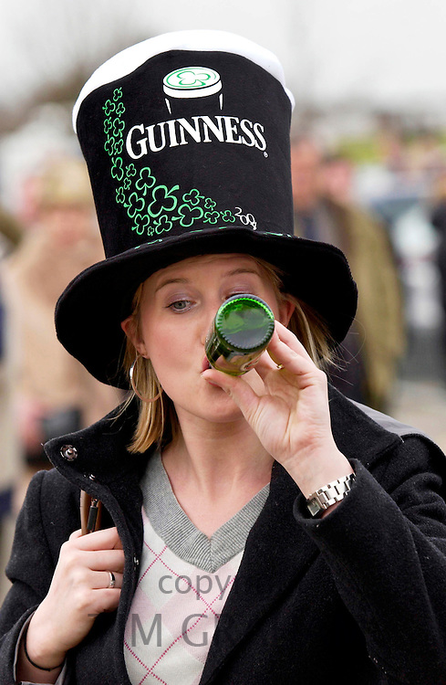 Racegoer wearing Guinness hat and drinking Guinness on St Patrick's Day at Cheltenham Races for the National Hunt Festival of Horseracing