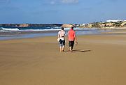 Man and woman walking together on sandy beach at Conil de la Frontera, Cadiz Province, Spain