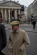 A commuter wearing a flat cap walks across Bank Triangle, on 9th February 2017, outside the Bank of England, in the City of London, England.