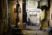 A man on a oldfashion motorbike in a street in Jodphur, India
