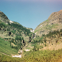 1. When was this photo taken? <br /> <br /> July 2004<br /> <br /> 2. Where was this photo taken? <br /> <br /> Southwest Colorado<br /> <br /> 3. Who took this photo? <br /> <br /> Terry Bliss<br /> <br /> 4. What are we looking at here? <br /> <br /> It was July 2004 and I recently bought my first big motorcycle, a black 2003 Victory Classic Cruiser, 1507 cubic centimeters of pure power. It was which handled beautifully despite its weight of 700 pounds. After a couple of days riding with my Colorado high school friends, I headed to Ouray to ride in the Southwest Victory Riders Rally. The ride went from Ouray to Durango. The total distance was only 70 miles but it was through some of the most beautiful scenery in Colorado. I thought I could handle it with no problem. I forgot that this route included the Million Dollar Highway, a narrow two-lane road that featured many switchback curves, no shoulders and sheer drop-offs. This 25 mile stretch is rated one of the most dangerous roads in the world. http://www.dangerousroads.org/north-america/usa/635-million-dollar-highway-usa.html. It is a perfect example of why Coloradans say there are no guardrails, the tourists keep knocking them down. These pictures were taken during a much needed break after the dangerous stretch of road to let my heart stop racing. This beautiful mountain valley overlooked several mountains including the ones I had just traversed.<br /> <br /> 5. How does this old photo make you feel? <br /> <br /> Nostalgic<br /> <br /> 6. Is this what you expected to see? <br /> <br /> Yes<br /> <br /> 7. Does this photo bring back any memories? <br /> <br /> Yes<br /> <br /> 8. How do you think others will respond to this photo? <br /> <br /> Want to visit the location.