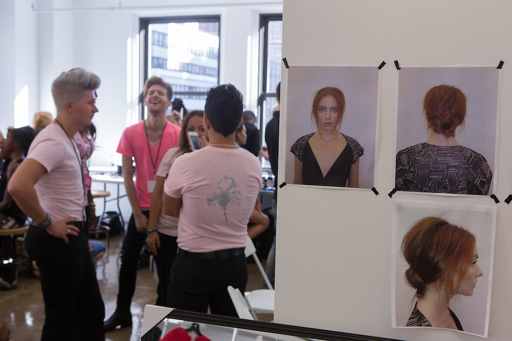 "Hairdressers and makeup artists chat beside a series of ""look"" photos backstage at the Carmen Marc Valvo Spring 2013 Fashion Week show in New York."