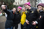 Portland Police Bureau officers Dan Spiegel (second from left)) and Mark Ellison pose with participants in Women's March on Portland on Saturday, Jan. 21, 2016 in downtown Portland, Ore. The march was held in support of a national women's march held in Washington, D.C.  Photo by Randy L. Rasmussen, © 2017.