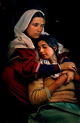 A mother, holding her daughter mourns the death of her son who was thought to be a militant. Guerrilla violence in Kashmir has slowed but it is a fragile peace between India and Pakistan, who both claim the Himalayan region.