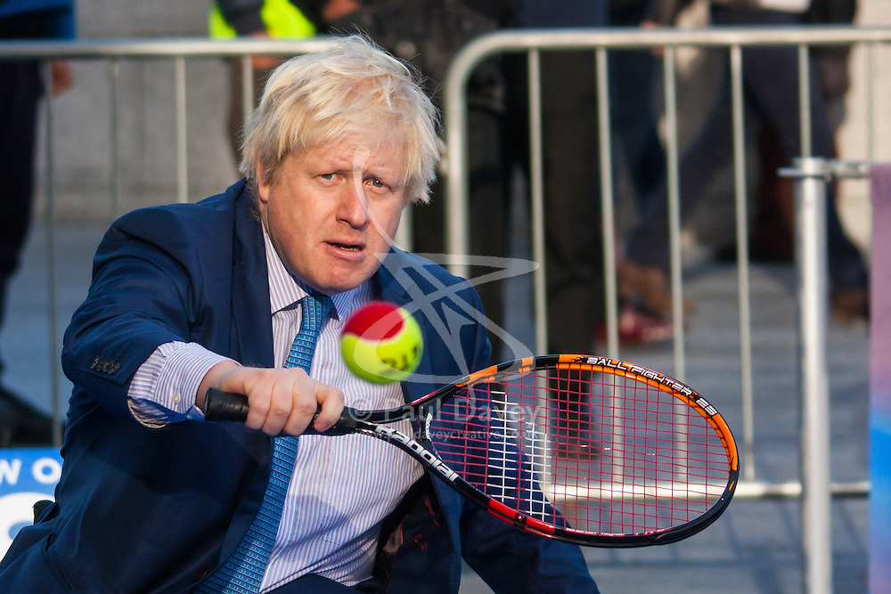 City Hall, London, November 24th 2014. Mayor Boris Johnsonwelcomes the world's best wheelchair tennis players with a game of mini tennis outside City Hall. The players are in London to compete in the NEC Wheelchair Tennis Masters 2014, being held at the Lee Valley Hockey and Tennis Centre, being held from 26 - 30 November. PICTURED: Mayor Boris Johnson returns a serve in a game of wheelchair tennis.