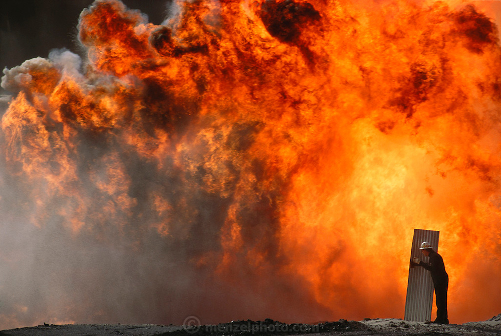 An oil well fire specialist from the Texas company Boots and Coots shields himself from the intense heat of the fire so that he can more closely direct other workers using equipment on the end of long booms attached to shielded bulldozers in the Kuwait oil fields. The company was one of those brought in to fight the Kuwait oil well fires after the end of the Gulf War. More than 700 wells were set ablaze by retreating Iraqi troops creating the largest man-made environmental disaster in history.