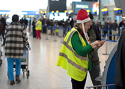 © Licensed to London News Pictures. 23/12/2016. London, UK.  A check in assistant wearing a Santa hat at Heathrow Airport, Terminal 5,  as the Christmas getaway begins, with stations, airports and roads expected to be very busy as people start their Christmas holidays. Photo credit: Ben Cawthra/LNP