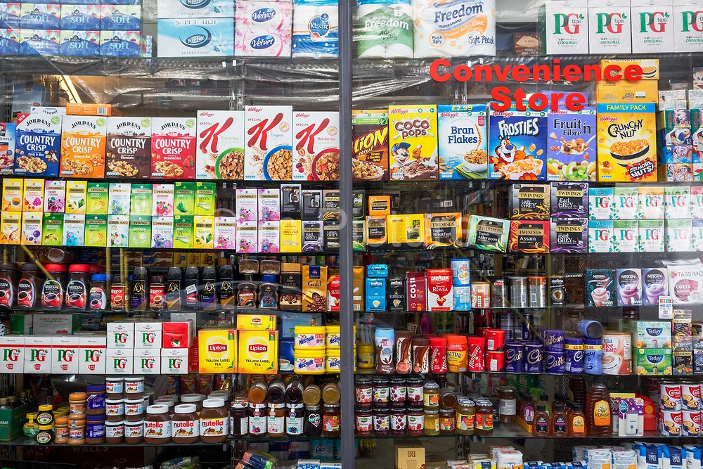 Window display showing the retail products being sold in a Kensington convenience store, on 31st August 2017, in London England.