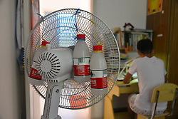 August 4, 2017 - Liaocheng, Liaocheng, China - Liaocheng, CHINA-August 4 2017: (EDITORIAL USE ONLY. CHINA OUT) ..A student invents a self-made 'air conditioner' by fastening iced water bottles behind an electric fan to enjoy cool during the hottest day in Liaocheng, east China's Shandong Province. (Credit Image: © SIPA Asia via ZUMA Wire)