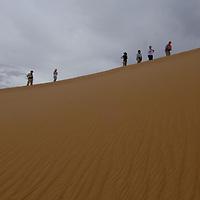 Geo-tourists climb a sand dune in the southern Gobi Desert.