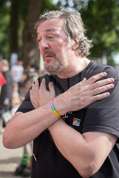 "© Licensed to London News Pictures . 10/08/2013 . London , UK . STEPHEN FRY illustrates a hand gesture which he suggests athletes at the Sochi Games use to indicate their support for gay Russians . Protesters with placards . Demonstration against homophobic laws being enacted in Russia on Whitehall this afternoon (10th August 2013) . Legislation includes banning gay pride events for100 years , banning the distribution of "" propaganda of non-traditional sexual relations "" to minors , making it illegal for the adoption of Russian children by gay couples or any single person who comes from a country that recognises marriage equality and giving authorities the rights to arrest foreign nationals whom they suspect are LGBT or pro gay with the right to detain them for up to 14 days. Photo credit : Joel Goodman/LNP"