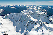 The Bailey Range in Olympic National Park, seen from a small plane at about 1000 feet over the peaks. Mount Olympus is the tallest and most prominent mountain in the Olympic Mountains of western Washington state. Located on the Olympic Peninsula, it is the central feature of Olympic National Park. Elevation: 7,979 feet. First ascent: August 12, 1907<br /> <br /> Mt. Rainier can be seen in the distance to the northeast, looking to the SE.