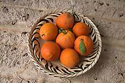 Bowl of fresh oranges on carpet, Morocco