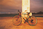 A bicycle leans against a street lamp on a road close to the coast of Tahiti