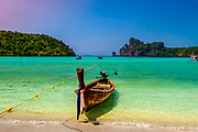 One longboat beached on a beautiful Phi Phi island. Not a cloud in the sky make the water beautiful. RAW to Jpg