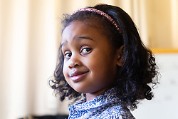 A cheeky grin from four-year-old Alannah George who has an IQ of 140 and taught herself to read at two-and-a-half, is a member of Mensa. Iver, Buckinghamshire, March 10 2019.