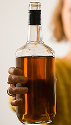 PICTURE POSED BY MODEL A woman holding a bottle of alcohol.