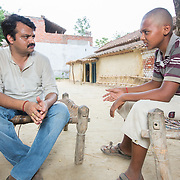 CAPTION: Ambarish Singh of PAHEL mentors prospective microentrepreneur Lucky Yadav, aged just 15, as he thinks through possibilities for starting a photography and video studio once SPEED brings electricity to the village of Baharayen. LOCATION: Baharayen, Faizabad District, Uttar Pradesh, India. INDIVIDUAL(S) PHOTOGRAPHED: From left to right - Ambarish Singh and Lucky Yadav.
