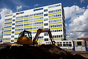 Construction site in front of a tower block in East London. A small JCB digger sits upon a mound of earth on a new construction site building new flats and apartments. Housing is a huge issue in London, in particular in Tower Hamlets, the most populated borough in the whole country.