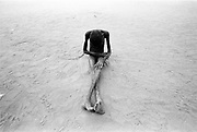 A young girl, possibly retarded or possibly, more likely, driven mad by hunger, sits playing in the sand. Ajiep, South Sudan