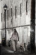 A man walks his dog down an alley in Flagstaff, Arizona.
