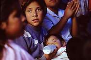Photojournalism: a young girl bottle feeds her little sister in a orphanage in Mexico.