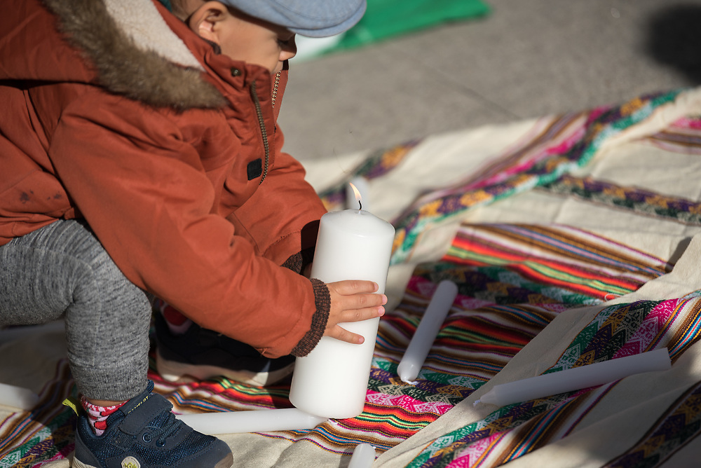 7 December 2019, Madrid, Spain: A young boy places a candle while people of faith gather in a 'Prayer for the Rainforest' as part of the Cumbre Social por el Clima, on the fringes of COP25 in Madrid, where faith-based organizations continue to urge decision-makers to take action for climate justice.