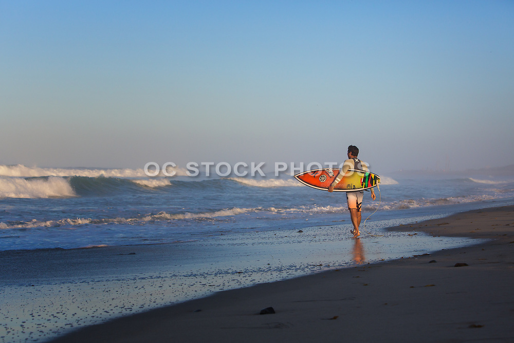 Adult Male Surfer Looking at Waves Carrying a Short Board