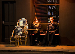 © Licensed to London News Pictures. 25/09/2020. London, UK. A couple sit next to stacked up chairs, outside a bar  on Portobello Road, Notting Hill, west London before before a  10pm curfew comes in to place as part of new restrictions intended to prevent the spread of COVID-19. Photo credit: Ben Cawthra/LNP