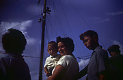 A mother holds her 3 year-old son during summer time in the early 1960s. Looking up from a low angle, see see the mother and her young son in sunlight, made dark by underexposure of the film, recorded on a camera by the boy's father, an amateur photographer in 1964. The mast and rigging of a small boat can be seen behind so they must be at the seaside, near from where they live in Southend-on-Sea in Essex. The sky is a deep blue and the shapes on their heads almost merge with the background. It was recorded on a film camera by the boy's father, an amateur photographer in 1962. The picture shows us a memory of nostalgia in an era from the last century.