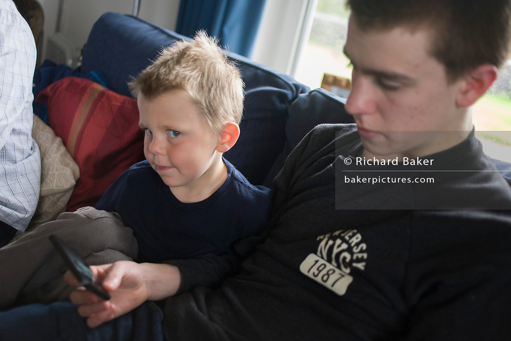 A 16 year-old teenager shows his 4 year-old cousin his smartphone on the family home sofa.
