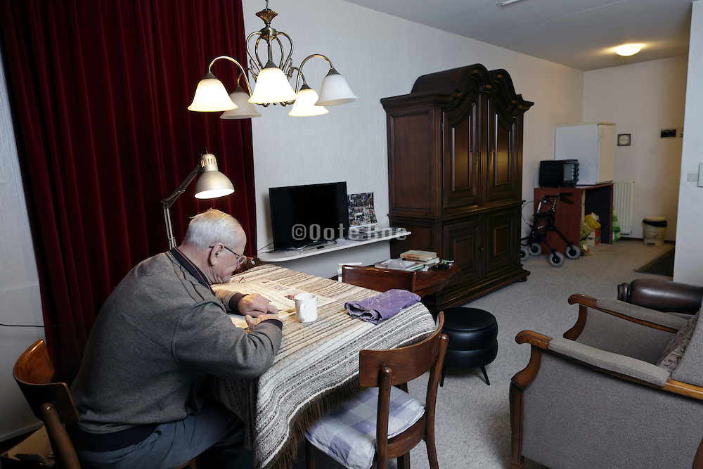 senior man drinking coffee and reading the newspaper in a independent living retirement home