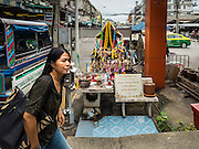 20 JULY 2015 - NONTHABURI, NONTHABURI, THAILAND:  A woman walks past a shrine at Bang Si Mueang Ferry Pier in Nonthaburi. The pier is in an area that is supposed to be redeveloped for the Chao Phraya Promenade project. The Chao Phraya promenade is development project of parks, walkways and recreational areas on the Chao Phraya River between Pin Klao and Phra Nang Klao Bridges. The 14 kilometer long promenade will cost approximately 14 billion Baht (407 million US Dollars). The project involves the forced eviction of more than 200 communities of people who live along the river, a dozen riverfront  temples, several schools, and privately-owned piers on both sides of the Chao Phraya River. Construction is scheduled on the project is scheduled to start in early 2016. There has been very little public input on the planned redevelopment.          PHOTO BY JACK KURTZ
