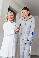 Patient with crutches prcticing to walk