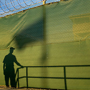 "The shadows of military officials and a flag are seen cast on a fence in Camp Delta at the detention facility in Guantanamo Bay, Cuba. Approximately 250 ""unlawful enemy combatants"" captured since the September 11, attacks on the United States continue to be held at the detention facility.(Image reviewed by military official prior to transmission)"