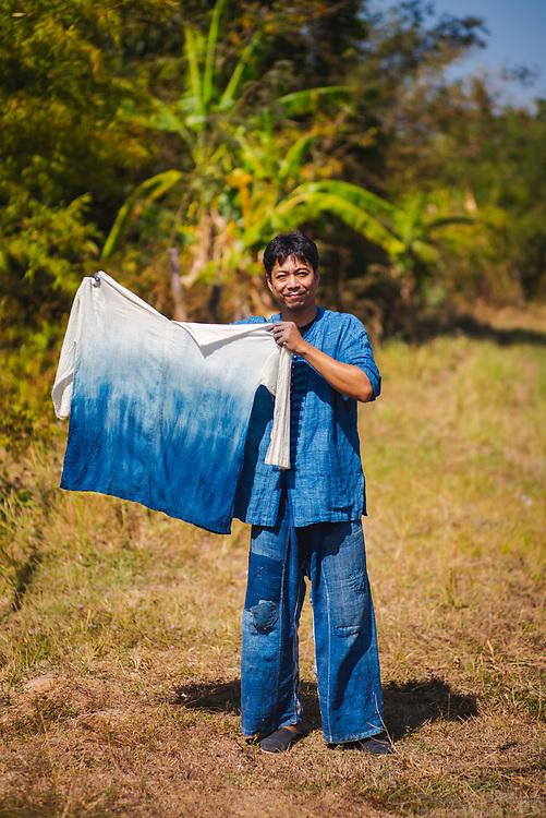 A man holding a shirt dyed with indigo using traditional methods, Indigo Dyeing Factory, Sakhon Nokhon, Thailand
