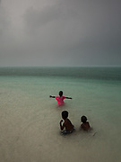 Kids playing in the ocean during a rainstorm. On Mantabuan island.