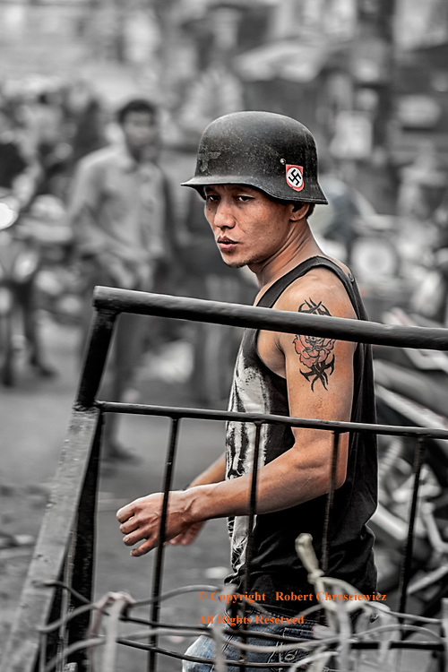 Thai Swastika (B&W&C):  The contrast between the western association of the Swastika with the notorious German Nazis and the Thai understanding of it being a revered Buddhist symbol could not be greater; yet in a strange way these two perceptions are brought together in this dramatic photograph (with selective colour) of a young man at work, wearing a German World War Two helmet with a prominently displayed Swastika, Chiang Rai Thailand.