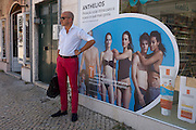 A man awaits city transport while standing in front of an ad for sunblock, in Lisbon, Portugal.