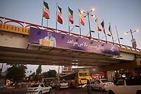 Iran, Ardabil, 21.08.2016: Autos und Passanten auf einer Kreuzung in Ardabil, Brücke mit Werbeplakat für eine Lebensversicherung, Iranische Fahnen. Provinz Ardabil, Nordwest-Iran.