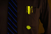 A glowing yellow highlighter leaves a stain on the pocket of a dress shirt. Blacklight photography.