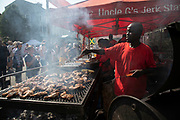 Jerk chicken cook at Notting Hill Carnival on 25th August 2019 in West London, United Kingdom. A celebration of West Indian / Caribbean culture and Europes largest street party, festival and parade. Revellers come in their hundreds of thousands to have fun, dance, drink and let go in the brilliant atmosphere. It is led by members of the West Indian / Caribbean community, particularly the Trinidadian and Tobagonian British population, many of whom have lived in the area since the 1950s. The carnival has attracted up to 2 million people in the past and centres around a parade of floats, dancers and sound systems.