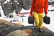 Glaciologists unload equipment from a helicopter at their field camp at the Columbia Glacier, near Valdez, Alaska.