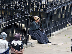 """Moray Place in Edinburgh's Georgian old town was turned into 19th century London for Julian Fellowes' new ITV show """"Belgravia"""".<br /> <br /> Pictured: An actress dressed as a maid checks her boots are laced up correctly but has to make some adjustments before she runs along the street. Here she takes a breather between takes.<br /> <br /> Alex Todd 
