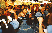 """Girls dancing flamenco and wearing traditional dress frilly flamenco dresses in the streets during the opening night of the Feria..The Feria de abril de Sevilla, """"Seville April Fair"""" dates back to 1847. During the 1920s, the feria reached its peak and became the spectacle that it is today. It is held in the Andalusian capital of Seville in Spain. The fair generally begins two weeks after the Semana Santa, Easter Holy Week. The fair officially begins at midnight on Monday, and runs six days, ending on the following Sunday. Each day the fiesta begins with the parade of carriages and riders, at midday, carrying Seville's citizens to the bullring, La Real Maestranza...For the duration of the fair, the fairgrounds and a vast area on the far bank of the Guadalquivir River are covered in rows of casetas (individual decorated marquee tents which are temporarily built on the fairground). Some of these casetas belong to the prominent families of Seville, some to groups of friends, clubs, trade associations or political parties. From around nine at night until six or seven the following morning, at first in the streets and later only within each caseta, crowds of people party and dance Sevillanas, traditional Flamenco dances, Sevillan style drinking Jerez sherry, or Manzanilla wine, and eating tapas. Men and women dress up in their finery, the traditional """"traje corto"""" (short jacket, tight trousers and boots) for men and the """"faralaes"""" or """"trajes de flamenca"""" (flamenco style dress) for women. The men traditionally wear hats called """"cordobés""""."""