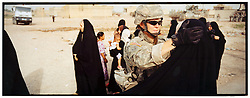 A female soldier attached to 4-14 Cavalry - a unit within the 172nd Stryker Brigade - searches women in the Baghdad Shiite neighborhood of Shula. The search - part of an operation by bolstered US and Iraqi forces in the hopes of getting a handle on the extraordinary numbers of sectarian killings in Baghdad - was carried out in Baghdad, Iraq on Sunday August 20, 2006. The brigade, which was in the process of rotating home at the end of a year tour in Mosul and northwestern Iraq, was diverted to the capital for an undetermined number of additional months.