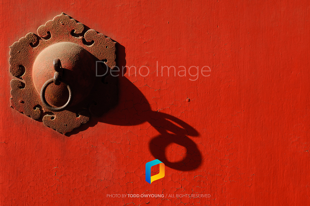 Detail of decorative hardware on a red door in China.
